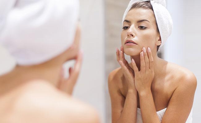 Mujer aplicando crema en cuello